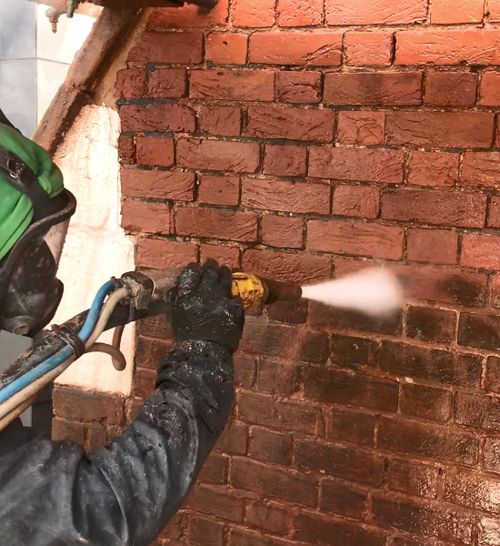 picture of brick cleaning specialist removing dirt from red brickwall