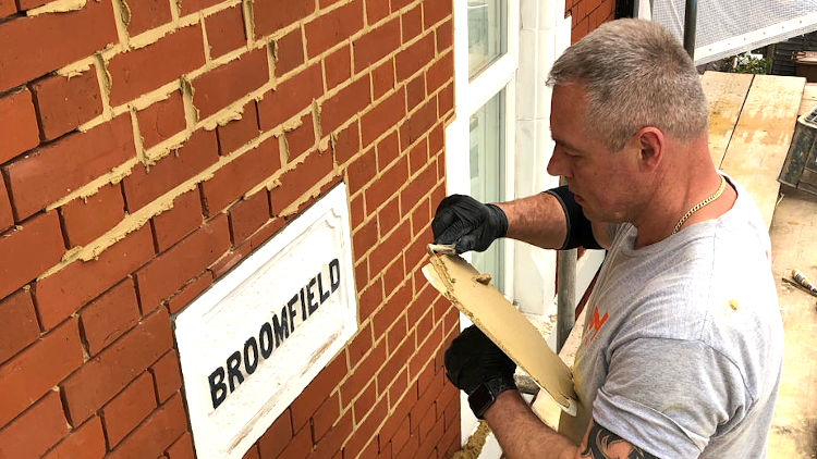 picture of man during repointing of red brick wall