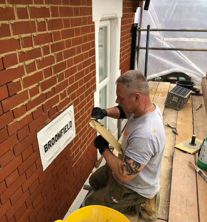 picture of man during repointing a red brick wall