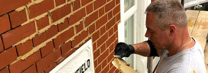 picture of brick restoration company employee during repointing red brickwall in london